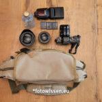 Mit einer spiegellosen Kamera passen die Kamera mit Objektiv, zwei weitere Objektive, ein großer Systemblitz (hier Godox) und Akkus plus Getränkeflasche in die beste Fototasche der Welt für kleines Gepäck.