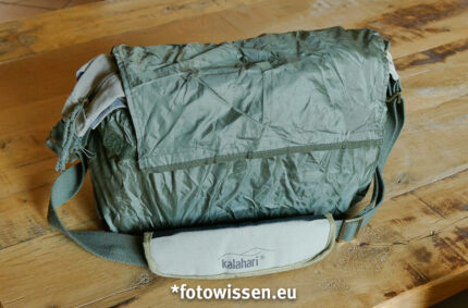 Der Regenüberzug ist in der hinteren Tasche mit Reißverschluss untergebracht. Er wird von unten nach oben über die Tasche gestülpt. Das ist ganz einfach... Die beste Fototasche für kleines Gepäck