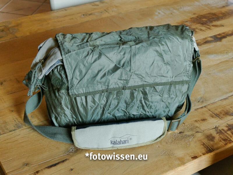 Der Regenüberzug ist in der hinteren Tasche mit Reißverschluss untergebracht. Er wird von unten nach oben über die Tasche gestülpt. Das ist ganz einfach...